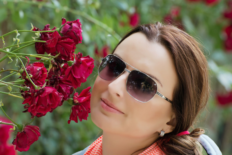 Beautiful woman in garden with red roses