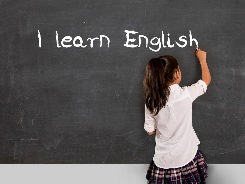 schoolgirl writing I learn English with chalk on blackboard school classroom