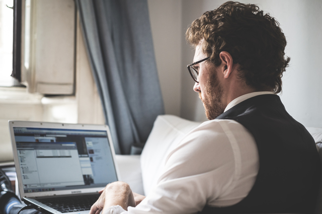 elegant attractive fashion hipster man using notebook