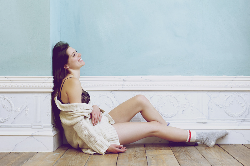 Smiling woman sitting on floor alone with underwear and sweater