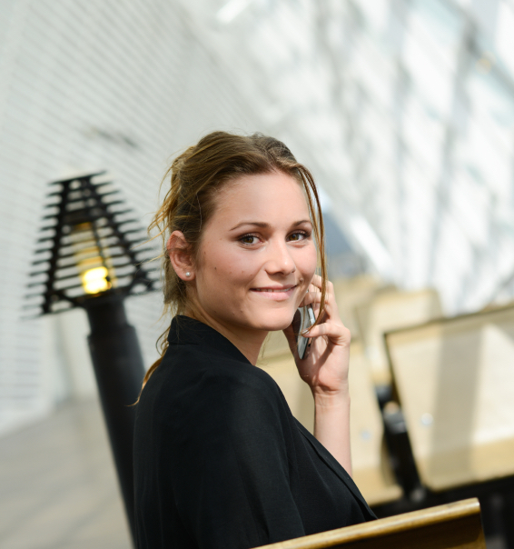 isolated portrait of cheerful young business woman in a public station