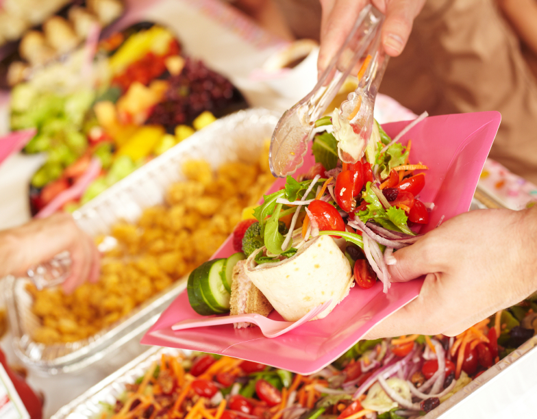 Woman Serving Vegetable Salad At Birthday Party
