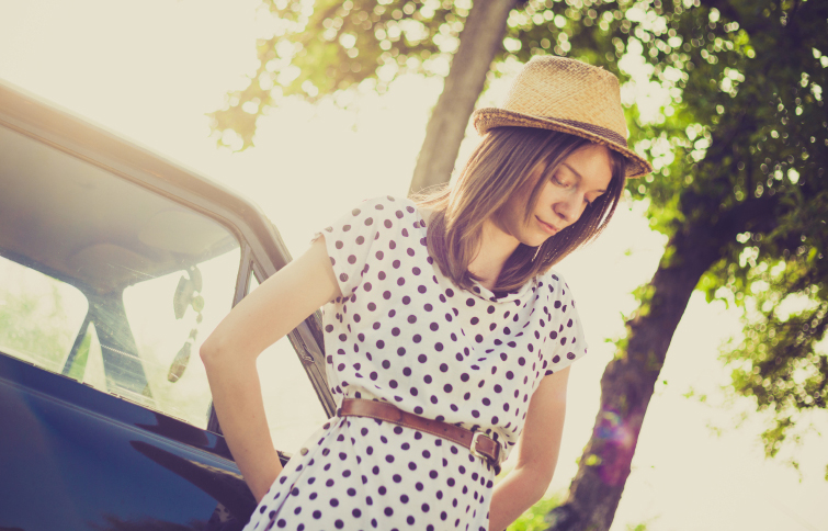 Retro style young woman standing next to the car