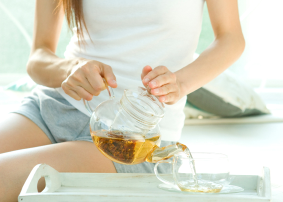 Woman pouring herb tea at bedside