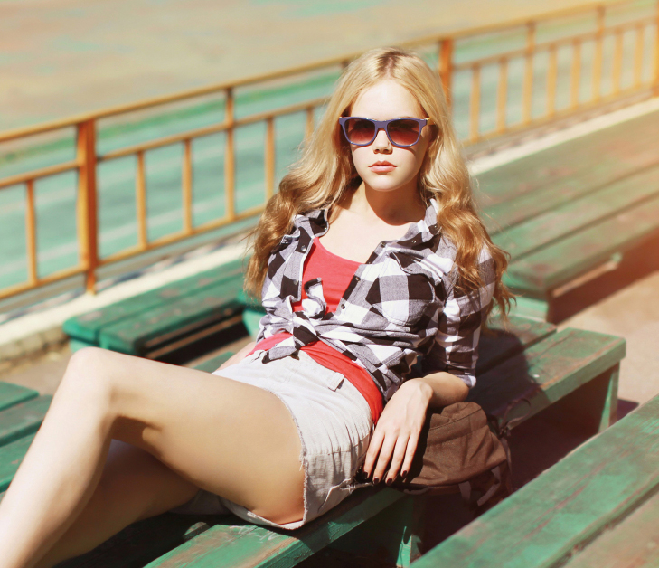 Pretty sexy hipster blonde woman in sunglasses posing outdoors i