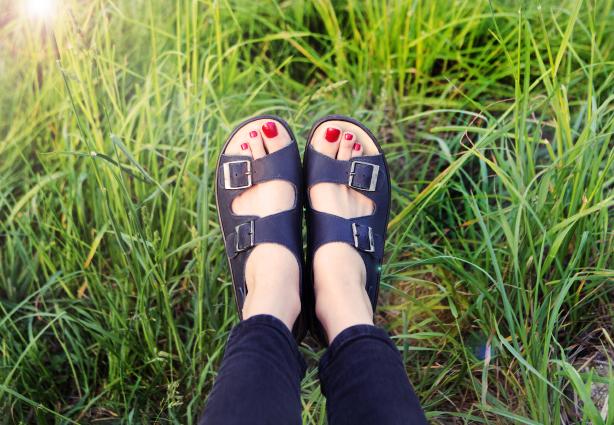 Woman  feet on green grass background