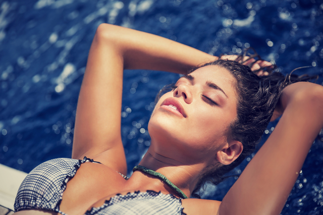 Woman tanning on the sailboat