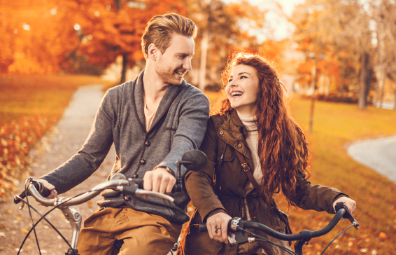 Ginger couple talking on bicycles during autumn day.