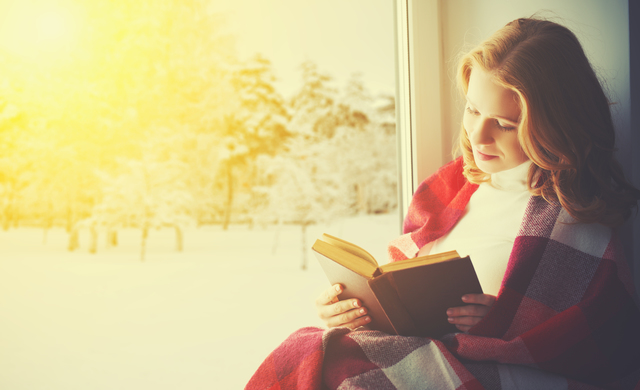 happy girl reading book by the window in winter
