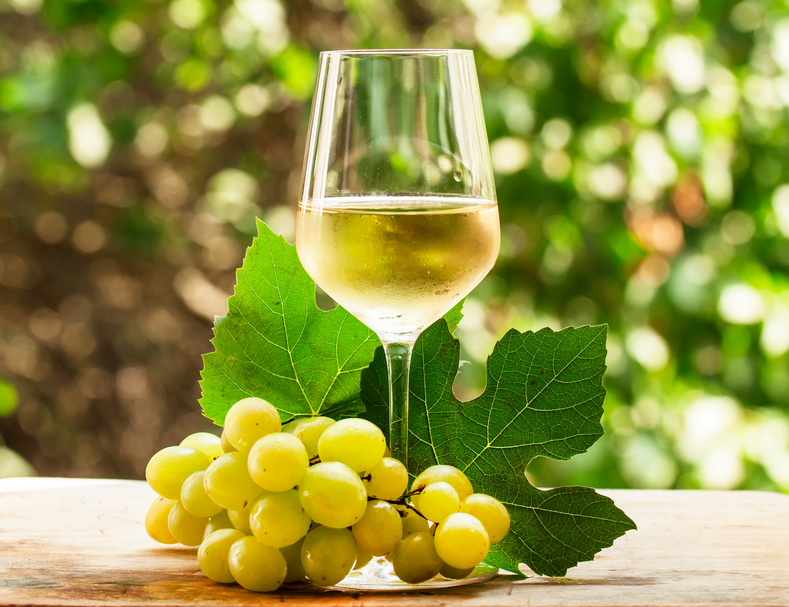 Coid white wine and green grapes on natural blurred background